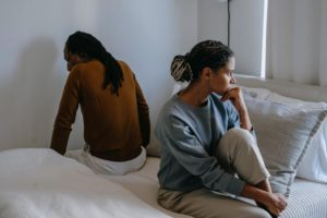 A couple sitting on the bed angry at themselves for not being able to communicate better