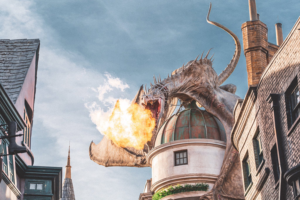 A dragon in the harry potter movie above a castle dome
