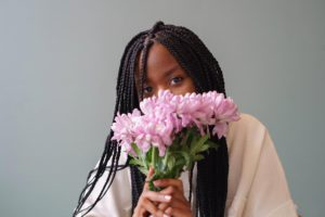 shy girl hides behind a bouquet of flowers