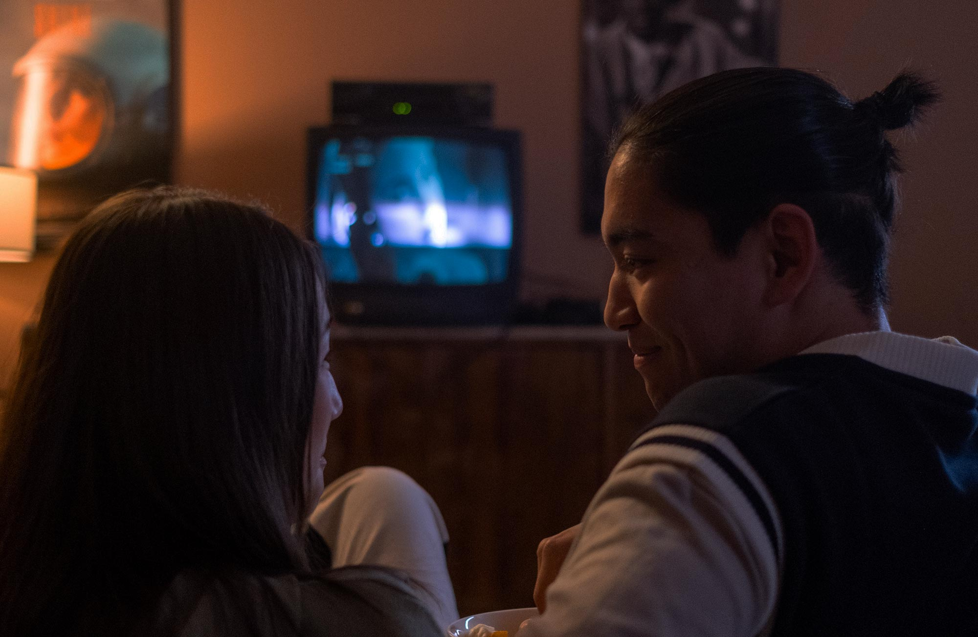A couple is watching a movie on the television